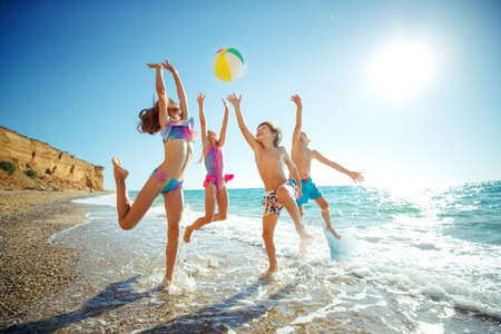 Cute kids having fun on the sandy beach in summer. High quality photo.