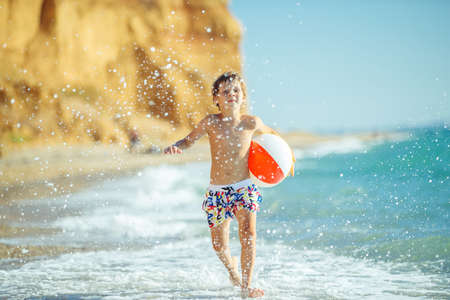Boy child has fun at sea. Summer, happiness, sea and a child with a ball. High quality photo.