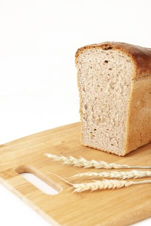Half a loaf of rye-wheat bread on a cutting board with ears of wheat. Bread, food, cooking, bakery products