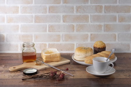 Picture of bakeries on the wooden table and brickwall in vintage style