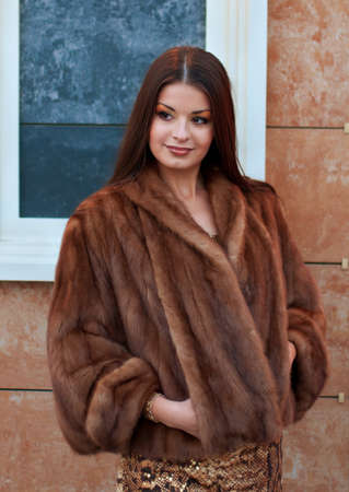 Portrait of luxurious young woman in a fur coat photo