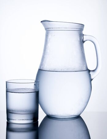 Pitcher of clear cold water with glass isolated on white background photo