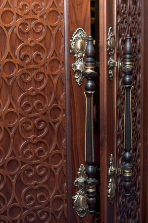 Handles on the old wooden door with carving