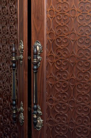 Handles on the old wooden door with carving photo