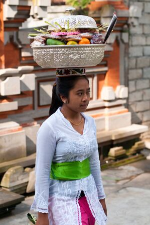 Tirta Empul, Bali, Indonesia - October 11, 2011  woman with basket on here head walking to Tirta Empul Temple to give offerings to the spirits
