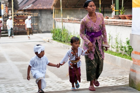 Tirta Empul, Bali, Indonesia - October 11, 2011  woman with here children walking to Tirta Empul Temple to give offerings to the spirits