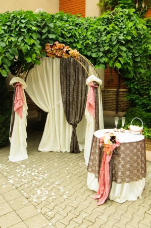 Outdoor wedding arch with table under grapewine photo