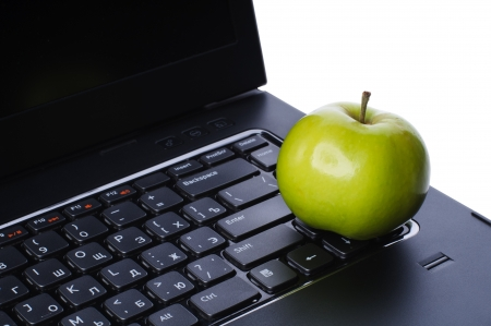 Green apple on laptop keyboard isolated on white background photo