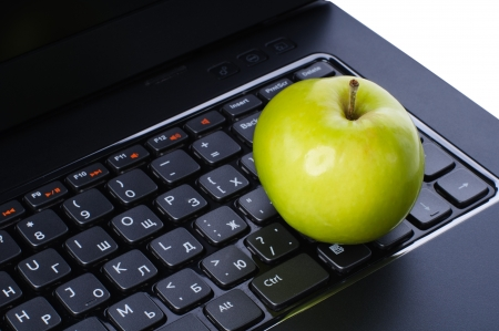 apple computer: Green apple on laptop keyboard isolated on white background Stock Photo