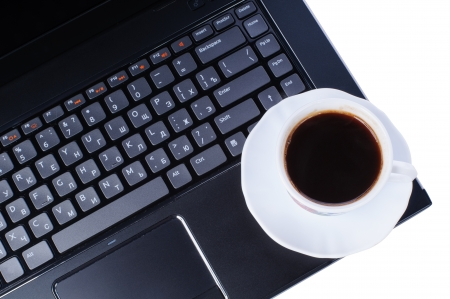 A cup of coffee on laptop keyboard isolated in white background photo