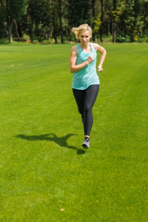 An active beautiful caucasian woman running outdoor in a park