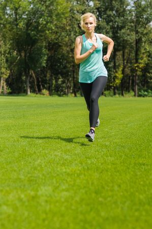 An active beautiful caucasian woman running outdoor in a park photo