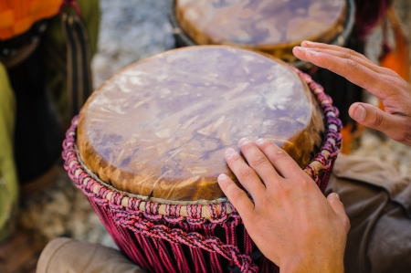 Man playing the djembe (african drum) outdoors photo