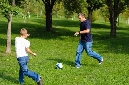 jugando al futbol: Ni�o jugando al f�tbol con su padre al aire libre