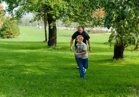 Young boy playing football with his father outdoors photo