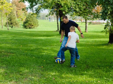father and son: Young boy playing football with his father outdoors