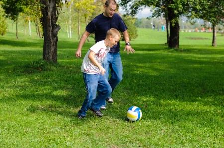 jugando futbol: Ni�o jugando al f�tbol con su padre al aire libre