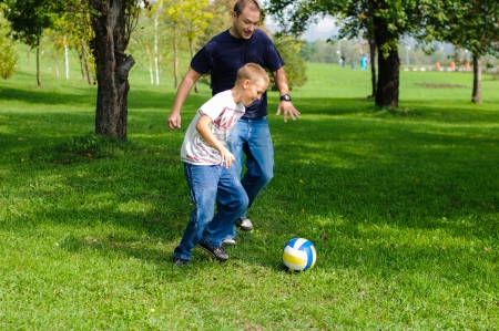 Young boy playing football with his father outdoors Stock Photo - 15315121