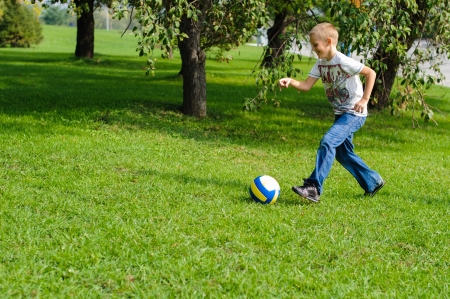 Young boy playing with his ball in the grass outdoors