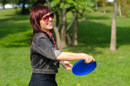 Young woman having fun with flying disc in the parking sunny summer day. Stock Photo