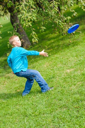 Little boy playing flying disc on green grass