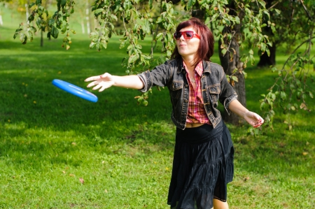 Young woman having fun with frisbee in the parkin sunny summer day. Stock Photo