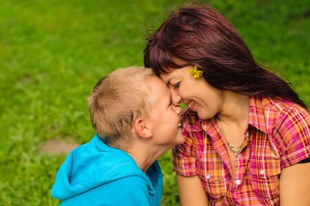 Mother and son play outside on field in the park photo