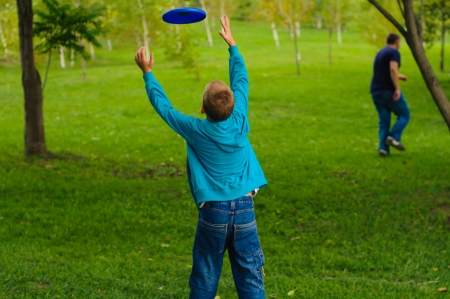 Little boy playing frisbee on green grass