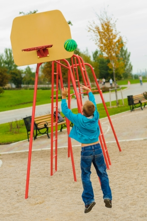 Young boy playing basketball at outdoors playground photo