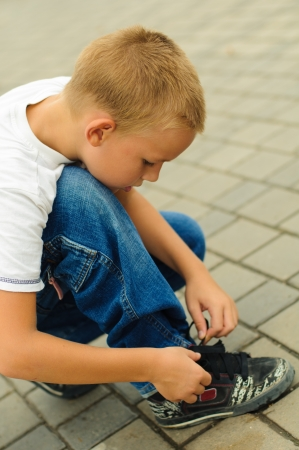 Boy tying the laces on his sneakers