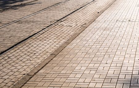 Cobblestone road in the sunlight with trams rails photo