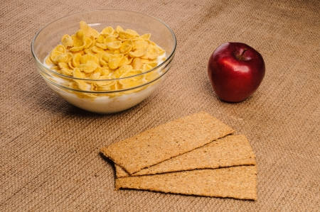 Bowl of cornflakes with milk, crispbreads and apple on sacking background photo