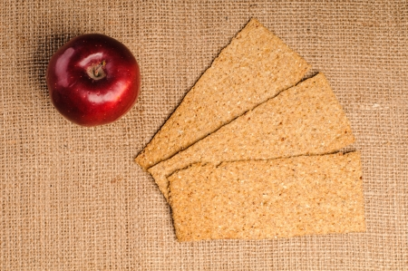 Red apple with crispbread on sacking background photo