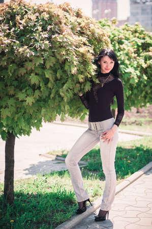 пышной листвой: Молодая женщина, стоя возле клена с пышной листвой Фото со стока