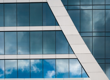 Blue sky reflected in the windows of office building photo