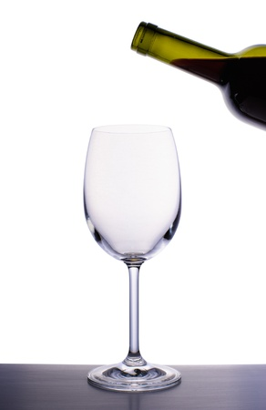 Empty wine glass and bottle of red wine isolated on white background Stock Photo