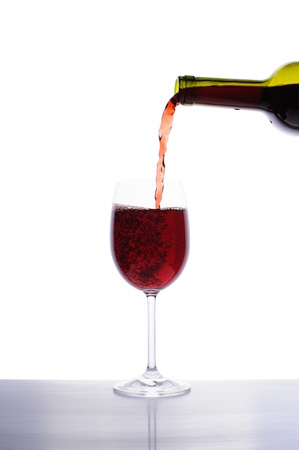 Red wine pouring into wine glass isolated on white background Stock Photo - 16646637