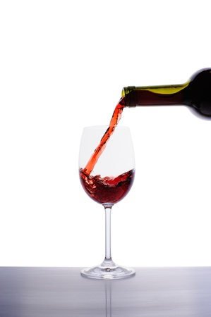 Red wine pouring into wine glass isolated on white background Stock Photo - 16646636