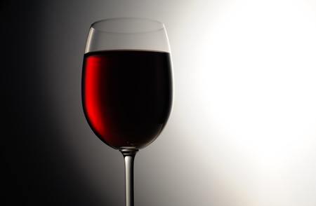 Closeup of red wine wineglass on dark background photo