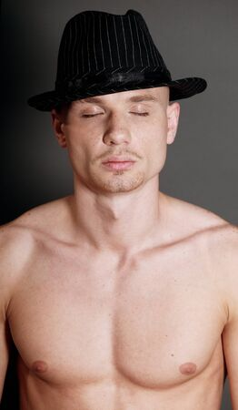 Studio portrait of young bald muscular man with black hat Stock Photo