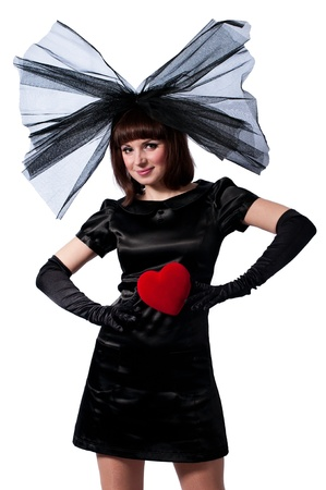 Pretty girl in black dress and big bow with red heart in her hands isolated on white background Stock Photo - 17429623