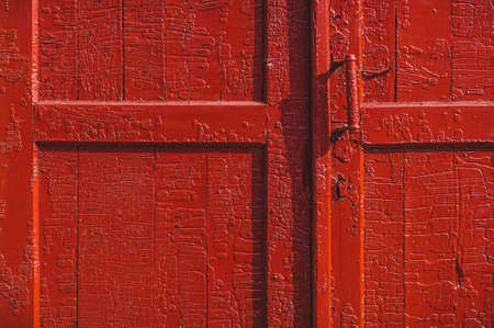 An old wood door with cracked red paint and grunge