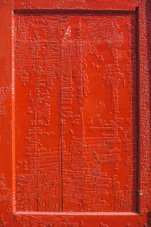 An old wood door panel with cracked red paint and grunge photo