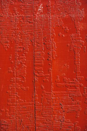 An old wood door panel with cracked red paint and grunge