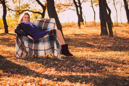 Young pregnant woman sitting on armchair in autumn forest