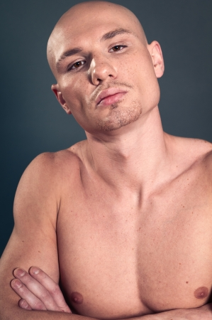 Portrait of naked athletic man posing over gray background