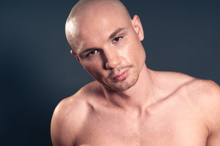 Studio portrait of shirtless muscled bald man photo
