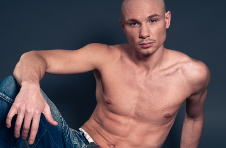 Portrait of naked athletic man posing over gray background photo