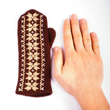 Brown woolen knitted mitten and hand on white background