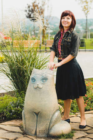 Young woman standing near funny cat statue in summer day
